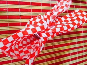 Cortar um retalho de chita num quadrado de 20cm x20cm e unir as pontas opostas em um nó