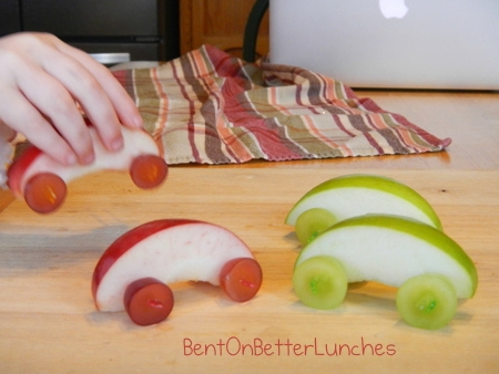 Carrinhos feitos com pedaços de maçã e rodinhas de uva